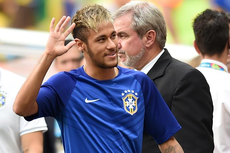 Brazil's injured forward Neymar waves at supporters as he arrives to sit on the bench before the third place play-off football match between Brazil and Netherlands during the 2014 FIFA World Cup at the National Stadium in Brasilia on July 12, 2014