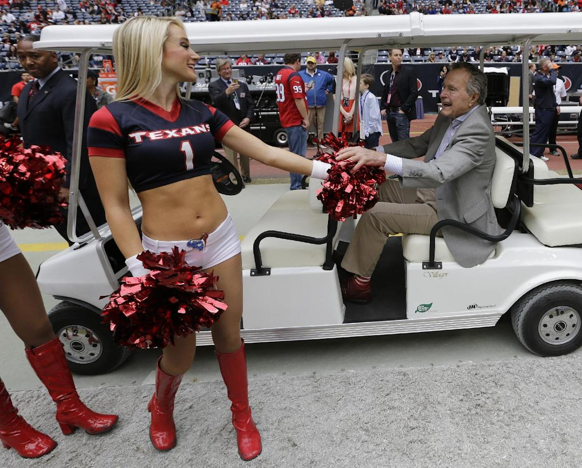 Former United States President George H. W. Bush, right, greets a Houston Texans cheerleader before an NFL football game against the New England Patriots, Sunday, Dec. 1, 2013, in Houston. (AP Photo/David J. Phillip)