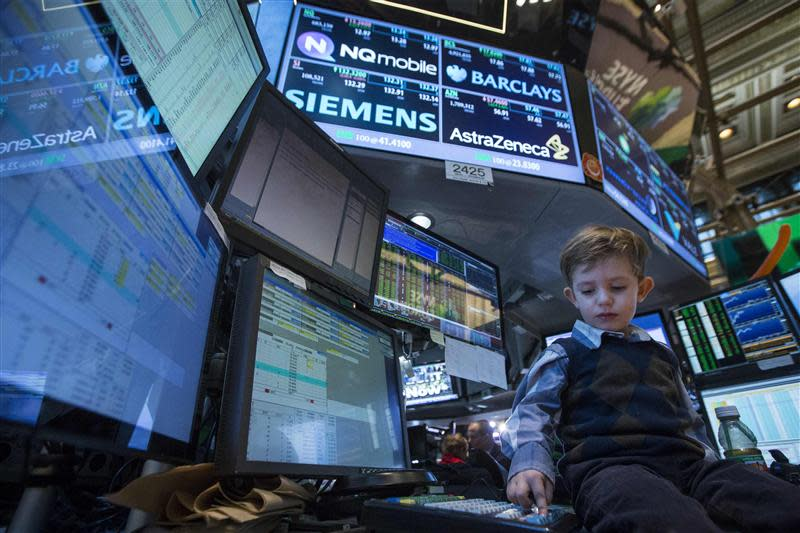 A young boy works at a trading post on the floor of the New York Stock Exchange