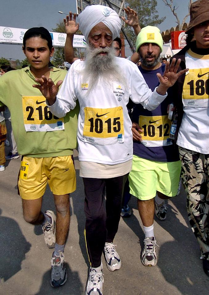 World's oldest marathon runner 94 year old Fauja Singh (C) runs at the start of the short version of 6 kilometers International Marathon in Lahore, 30 January 2005.  Singh who was born in Indian Punjab and now resides in London, has the unique distinction of taking part in record six full marathons in London, besides competing in similar events in other parts of the world.  AFP PHOTO/Arif ALI