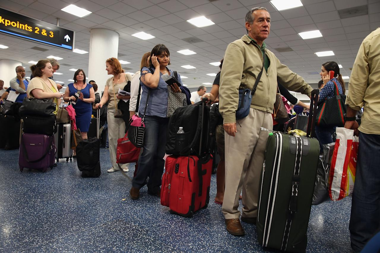 MIAMI, FL - APRIL 16:  American Airlines passengers  wait in line for a flight at Miami International Airport on April 16, 2013 in Miami, Florida. Thousands of American Airlines travelers became stranded today when the airline was forced to ground all its flights after a nationwide problem with its computer systems  (Photo by Joe Raedle/Getty Images)