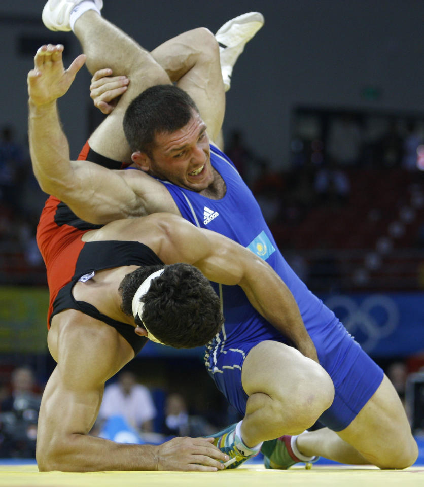 Georgia's George Gogshelidze, left, wrestles Kazakhstan's Taimuraz Tigiyev during their 96 kilogram freestyle wrestling match at the Beijing 2008 Olympics in Beijing, Thursday, Aug. 21, 2008.  (AP Photo/Ed Wray)