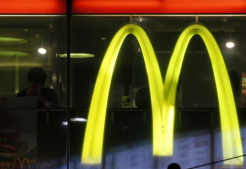 A customer using his mobile phone is seen next to a McDonald's logo in Tokyo