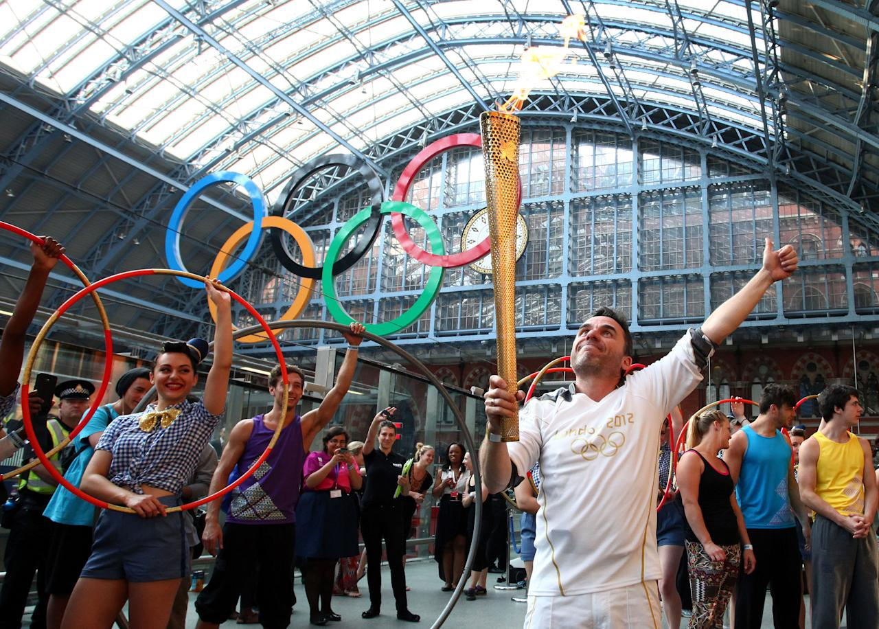 In this photo provided by LOCOG, Daniel Mccubbin holds the Olympic Flame inside St Pancras International Railway Station on Day 69 of the London 2012 Olympic Torch Relay, Thursday July 26, 2012, in London. (AP Photo/LOCOG, Gareth Fuller)