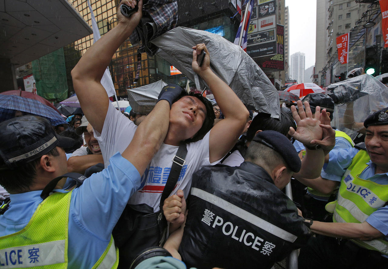 Protesters scuffle with police officers on a downtown street during an annual pro-democracy protest in Hong Kong Monday, July 1, 2013. Tens of thousands of the protesters demanded their widely disliked Beijing-backed leader resign and pressing for promised democratic reforms so they can choose their own top representative. The march is an annual event that underscores the growing gulf between Hong Kong and the mainland 16 years after the city ceased to be a British colony and came back under Beijing's control. (AP Photo/Vincent Yu)