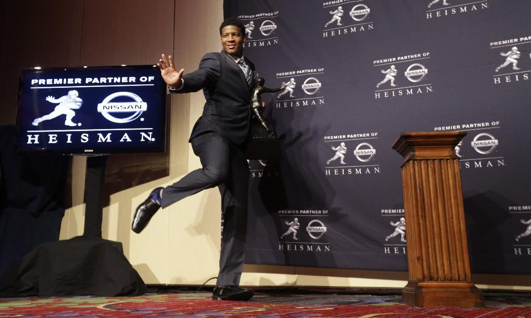 Florida State quarterback Jameis Winston does the Heisman Trophy pose for photographers after winning the award on Saturday, Dec. 14, 2013, in New York. (AP Photo/Julio Cortez)