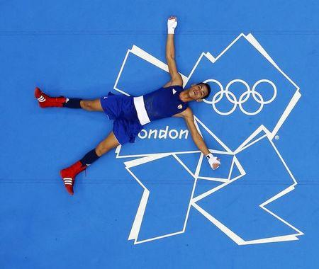 Cuba's Robeisy Ramirez Carrazana lays on the canvas after he was declared the winner over Mongolia's Tugstsogt Nyambayar following their Men's Fly (52kg) gold medal boxing match at the London Olympics August 12, 2012. REUTERS/Murad Sezer/Files