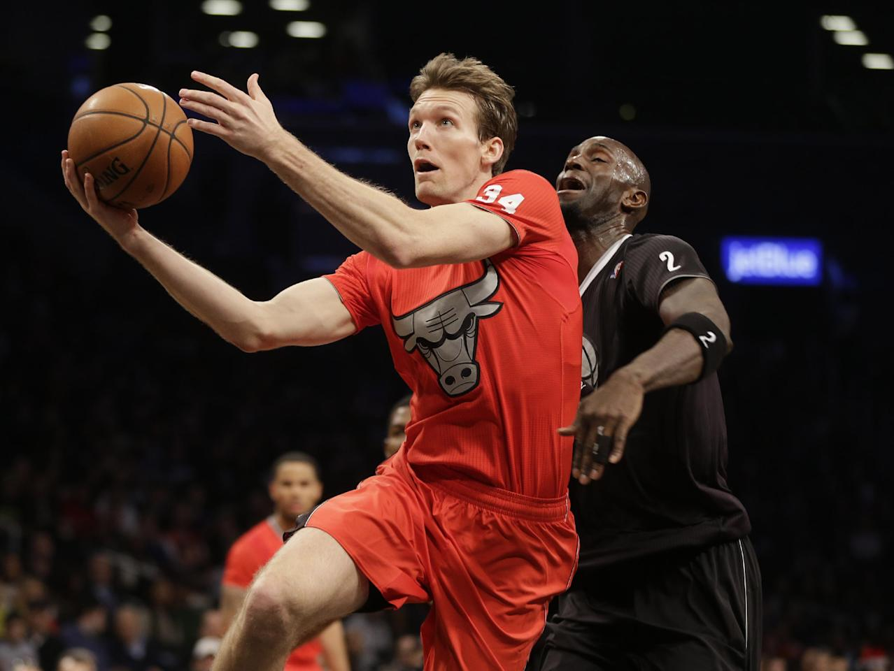 Chicago Bulls' Mike Dunleavy, left, drives to the basket past Brooklyn Nets' Kevin Garnett during the first half of the NBA basketball game at the Barclays Center Wednesday, Dec. 25, 2013, in New York. (AP Photo/Seth Wenig)