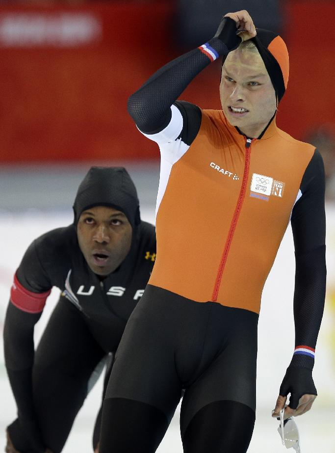 Shani Davis of the U.S., rear, and Koen Verweij of the Netherlands look at the scoreboard at the end of their men's 1,000-meter speedskating race at the Adler Arena Skating Center during the 2014 Winter Olympics in Sochi, Russia, Wednesday, Feb. 12, 2014. (AP Photo/Pavel Golovkin)