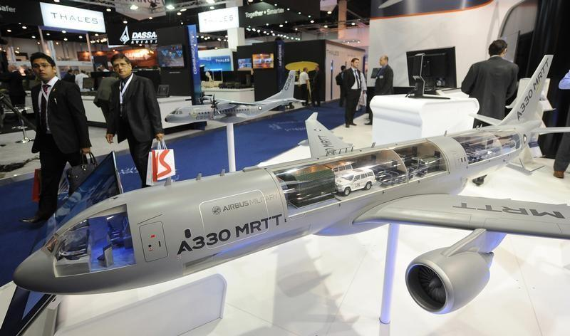 Visitors walk past a miniature model of the Airbus A330 MRTT during the IDEX at the Abu Dhabi National Exhibition Centre
