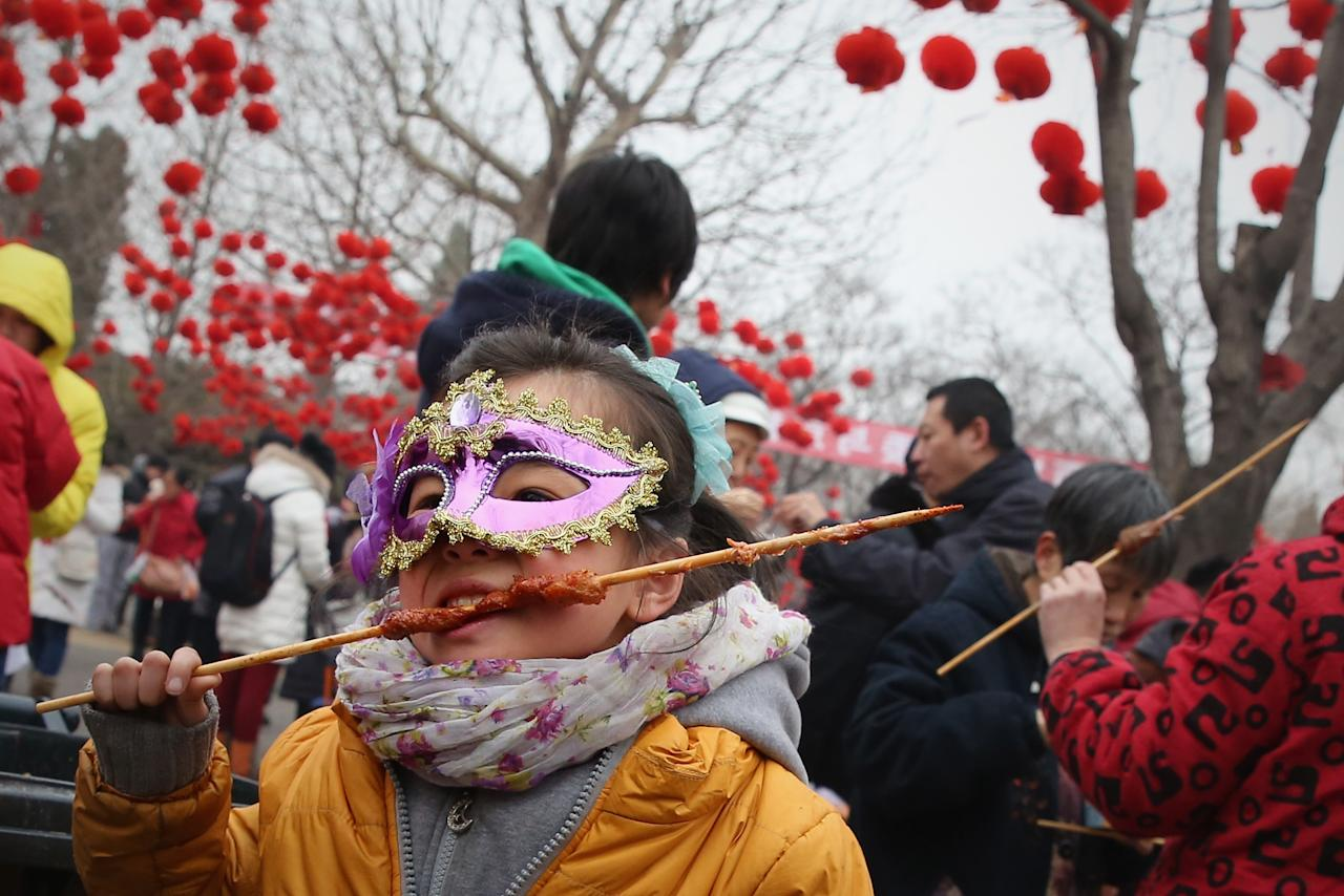 BEIJING, CHINA - FEBRUARY 11:  A liitle girl eats mutton skewer at a Spring Festival Temple Fair for celebrating Chinese Lunar New Year of Snake on February 11, 2013 in Beijing, China. The Chinese Lunar New Year of Snake also known as the Spring Festival, which is based on the Lunisolar Chinese calendar, is celebrated from the first day of the first month of the lunar year and ends with Lantern Festival on the Fifteenth day.  (Photo by Feng Li/Getty Images)