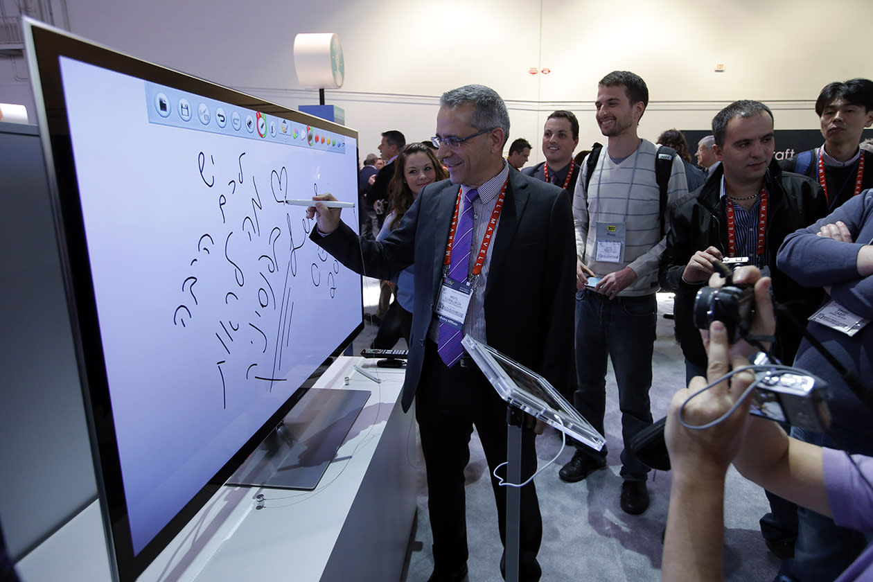 Moti Elmaliach, center, of Israel, writes on a display using Panasonic's electronic touch pen at the Panasonic booth at the International Consumer Electronics Show.