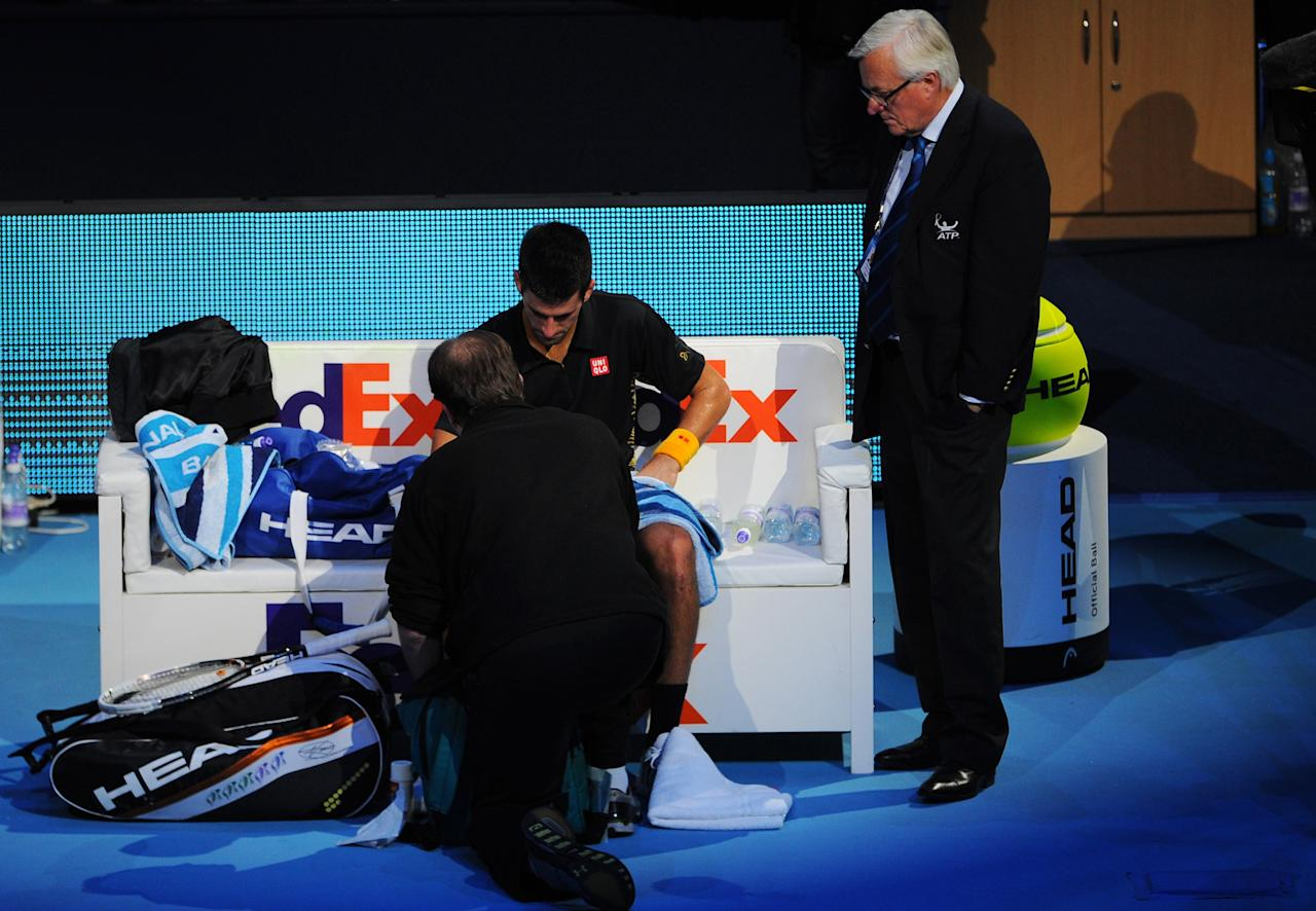 LONDON, ENGLAND - NOVEMBER 12:  Novak Djokovic of Serbia receives assistance for an injury after diving to reach a shot during his men's singles final match against Roger Federer of Switzerland during day eight of the ATP World Tour Finals at O2 Arena on November 12, 2012 in London, England.  (Photo by Michael Regan/Getty Images)