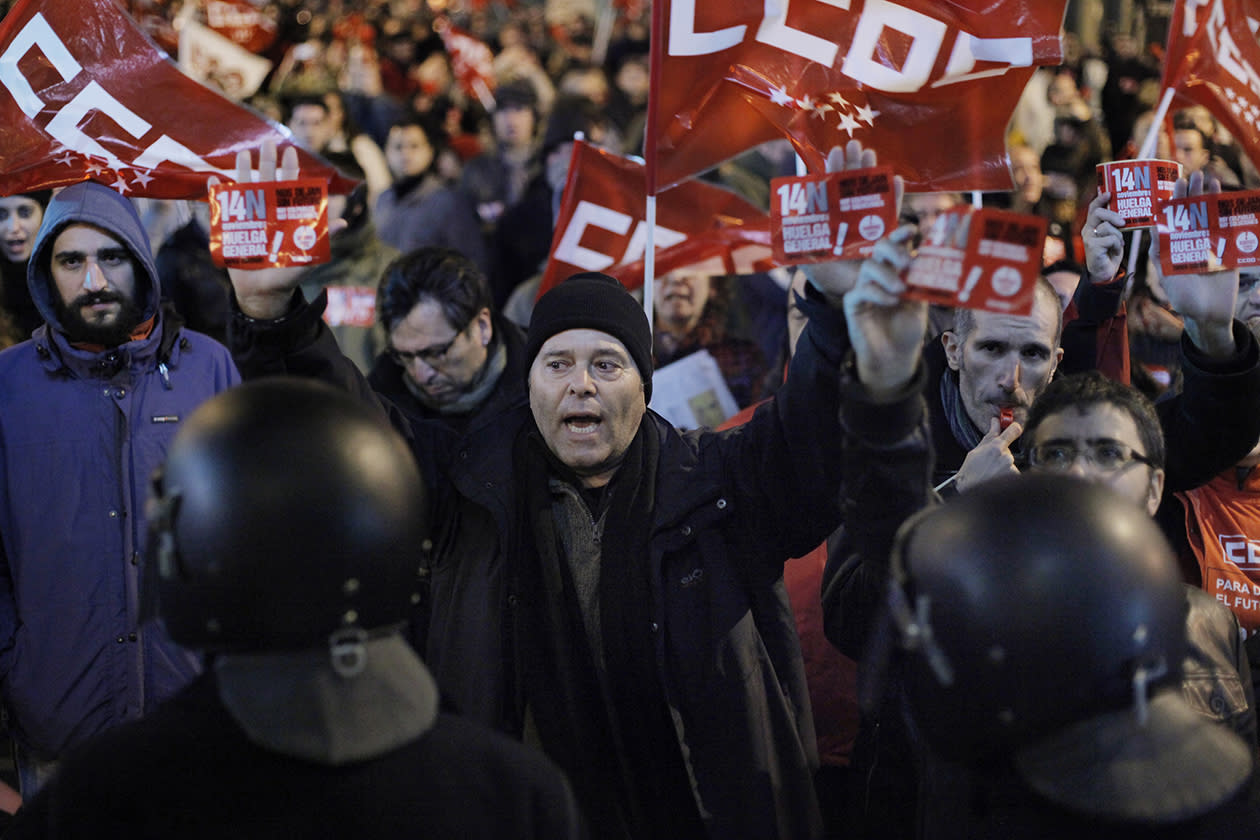 A protester shouts slogans in front of an open shop as police stand guard during a general strike in Madrid.