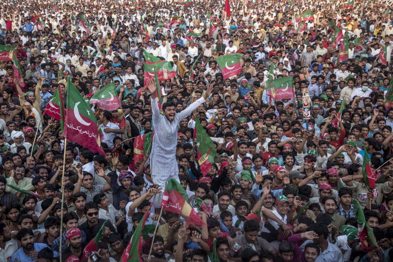 NAROWAL, PAKISTAN - MAY 02: Supporters of Imran Khan, chairman of the Pakistan Tehreek e Insaf (PTI) party, cheers and wave flags during an election campaign rally on May 01, 2013 in Narowal, Pakistan. Pakistan's parliamentary elections are due to be held on May 11. Imran Khan of Pakistan Tehreek e Insaf (PTI) and Nawaz Sharif of the Pakistan Muslim League-N (PMLN) have been campaigning hard in the last weeks before polling. (Photo by Daniel Berehulak/Getty Images)