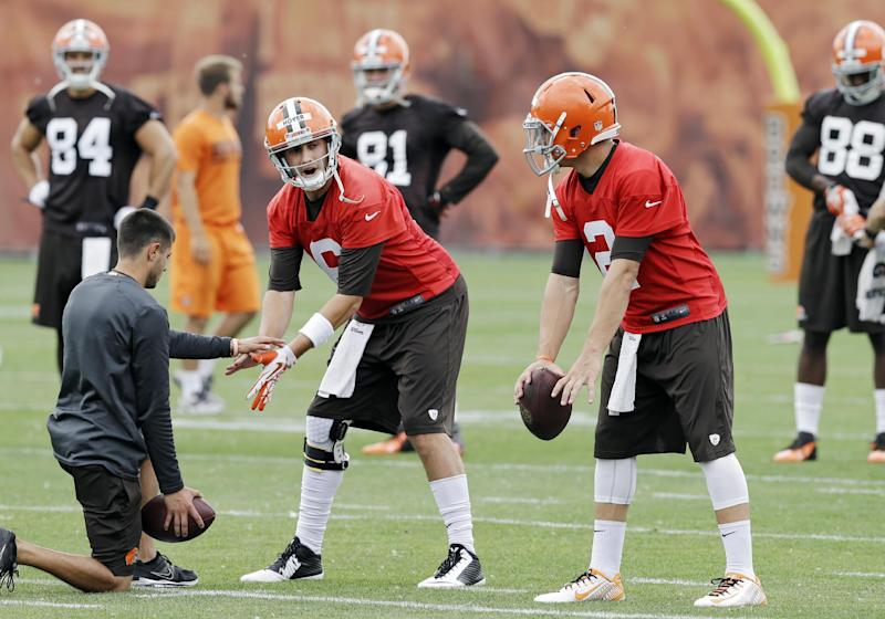Cleveland Browns quarterback Brian Hoyer, left, and Johnny Manziel runs a passing drill during a mandatory minicamp practice at the NFL football team's facility in Berea, Ohio Wednesday, June 11, 2014