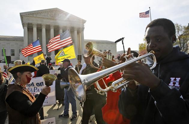 Jonathan Neal, a senior at Howard University, plays his trumpet in support of health care reform in front of the Supreme Court.