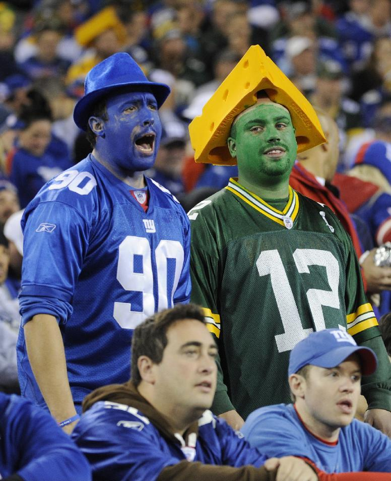 A New York Giants fan and a Green Bay Packers fan watch the first half of an NFL football game Sunday, Nov. 17, 2013, in East Rutherford, N.J.  (AP Photo/Bill Kostroun)