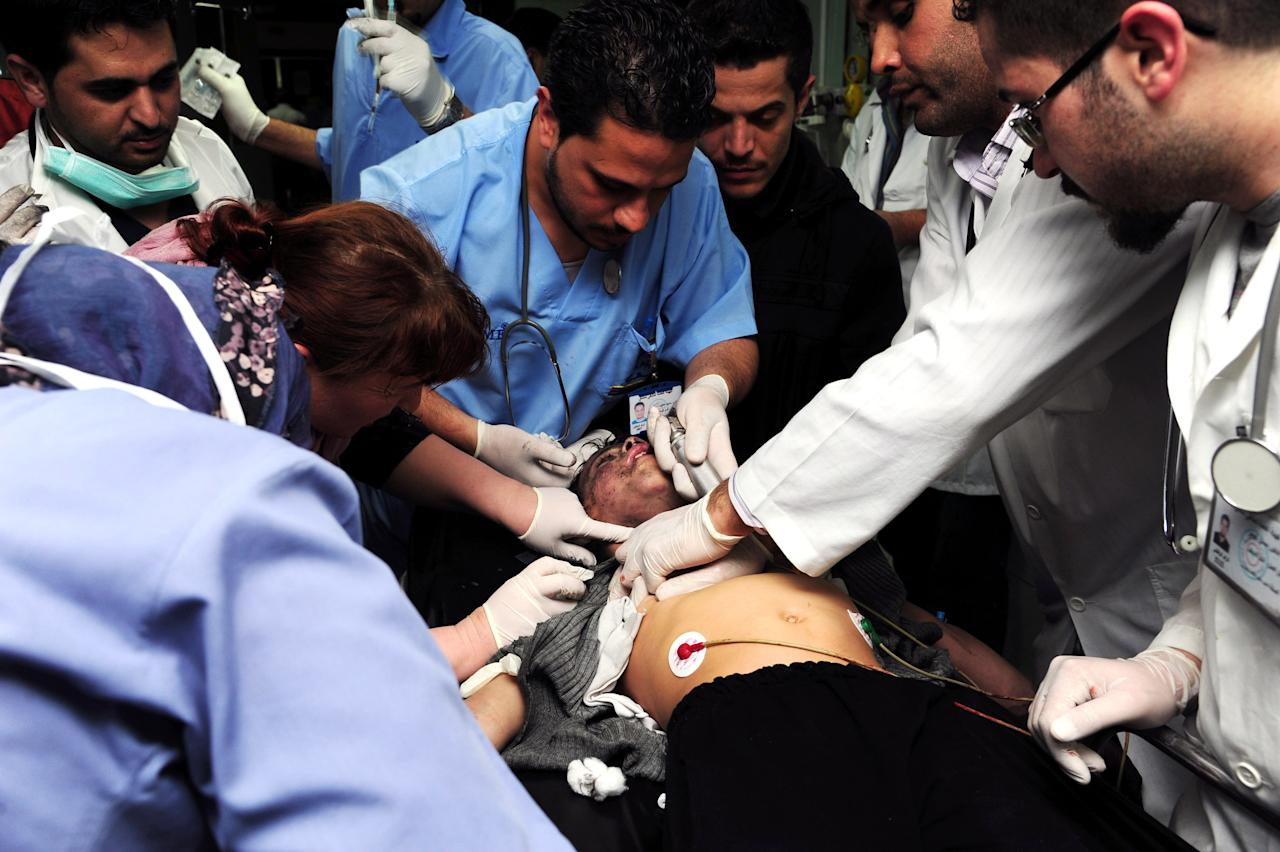 FILE - In this Wednesday, March 13, 2013 photo released by the Syrian official news agency SANA, Syrian doctors treat a man who was wounded at the scene where two mortar rounds exploded near an orphanage, at al-Boukhtyar area, in Damascus, Syria. More than 6,000 people were killed in the Syrian civil war in March alone, according to a leading activist group that reported it was the deadliest month yet in the 2-year-old conflict. (AP Photo/SANA, File)