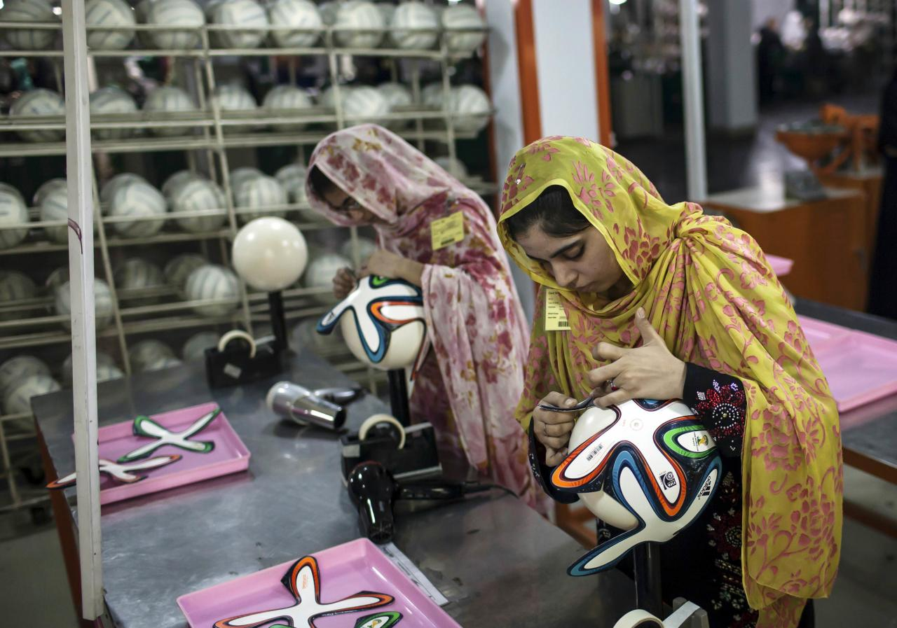 An employee adjusts outer panels on a soccer ball inside the soccer ball factory that produces official match balls for 2014 World Cup in Brazil, in Sialkot, Punjab province May 16, 2014. It was when he felt the roar of the crowd at the 2006 World Cup in Germany that Pakistani factory owner Khawaja Akhtar first dreamt up a goal of his own: to manufacture the ball for the biggest soccer tournament on the planet. Last year he finally got his chance - but only 33 days to make it happen. Picture taken May 16. REUTERS/Sara Farid (PAKISTAN \ - Tags: SPORT SOCCER WORLD CUP BUSINESS EMPLOYMENT)