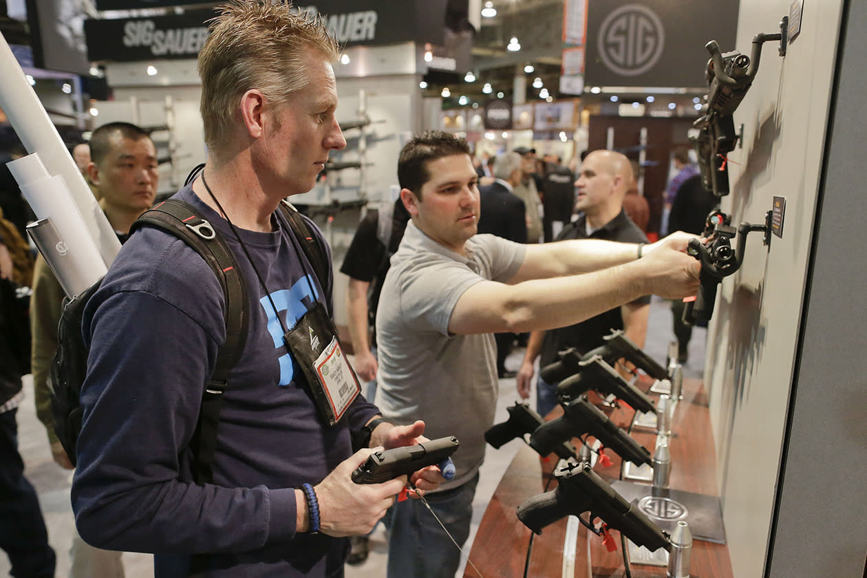 Randy Hancey, left, and Jaron Studley, both police officers from Ivins, Utah, examine several Sig Sauer law enforcement model pistols and rifles on display.