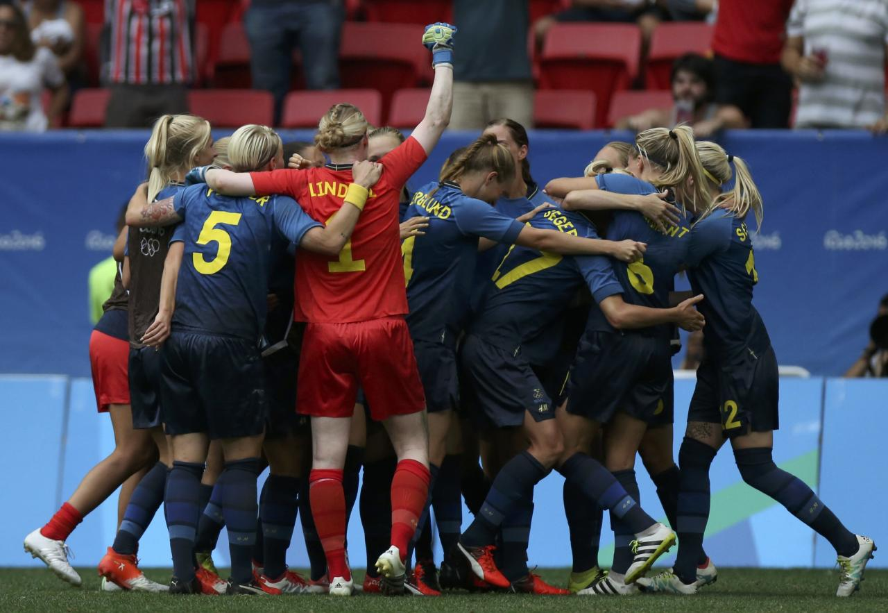 2016 Rio Olympics - Soccer - Quarterfinal - Women's Football Tournament Quarterfinal - Mane Garrincha Stadium - Brasilia, Brazil - 12/08/2016.  Swedish players crowd around goalie Hedvig Lindahl (SWE) of Sweden (1) as they celebrate after the game. REUTERS/Ueslei Marcelino FOR EDITORIAL USE ONLY. NOT FOR SALE FOR MARKETING OR ADVERTISING CAMPAIGNS.