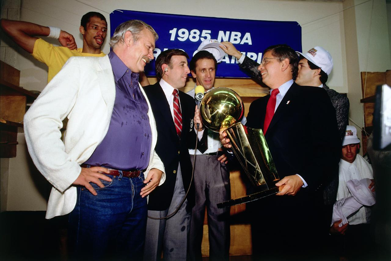 <p>NBOSTON - JUNE 9: NBA Commissioner David Stern presents the championship trophy to Lakers owner Jerry Buss while the Los Angeles Lakers celebrate in the locker room after winning the 1985 NBA Finals against the Boston Celtics on June 9, 1985 in Boston, Massachusetts. Lakers 111 vs Celtics 100. NOTE TO USER: User expressly acknowledges and agrees that, by downloading and/or using this Photograph, user is consenting to the terms and conditions of the Getty Images License Agreement. Mandatory Copyright Notice: Copyright 1985 NBAE (Photo by Andrew D. Bernstein/NBAE via Getty Images)</p>