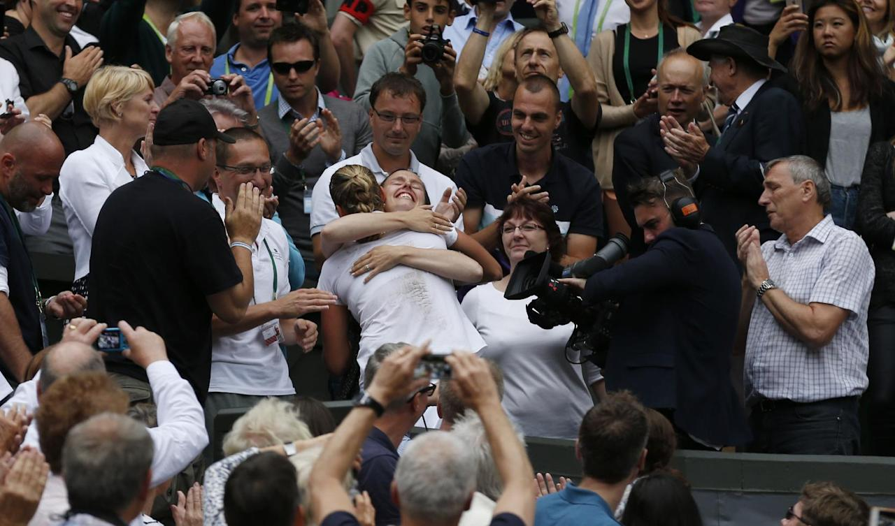 Petra Kvitova of Czech Republic embraces her family and friends in her players box as she celebrates defeating Eugenie Bouchard of Canada in their women's singles final at the All England Lawn Tennis Championships in Wimbledon, London, Saturday July 5, 2014. (AP Photo/Sang Tan)