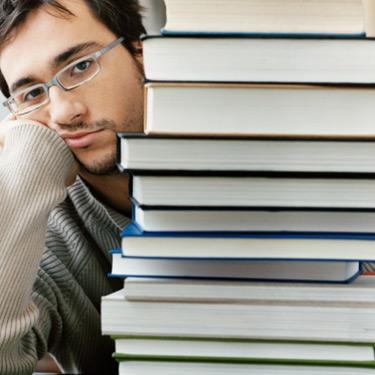 Bored-student-behind-a-stack-of-books_web
