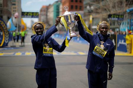 Women's division winner Kiplagat and men's division winner Kirui pose with the trophy at the finish line of the 121st Boston Marathon in Boston