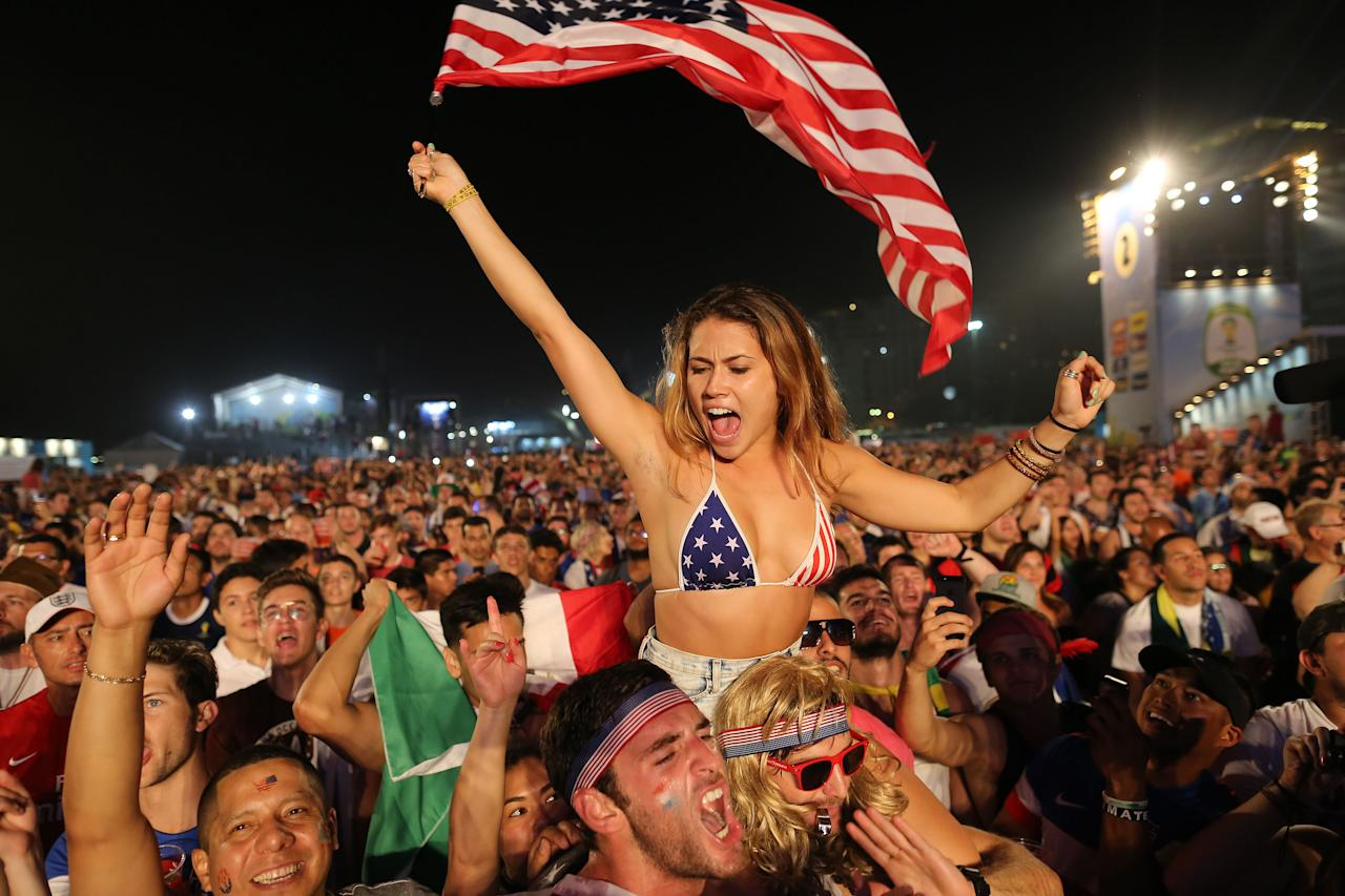 Soccer fans of the U.S. national soccer team cheer minutes before a live broadcast of the soccer World Cup match between USA and Ghana, inside the FIFA Fan Fest area on Copacabana beach, Rio de Janeiro, Brazil, Monday, June 16, 2014. (AP Photo/Leo Correa)