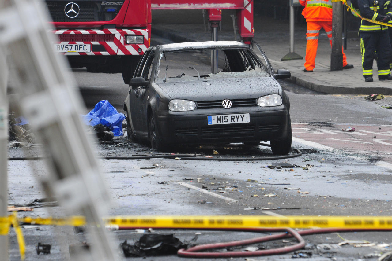 A damaged car remains in the street after a helicopter crashed into a construction crane on top of St George's Wharf tower building, in London, Wednesday Jan. 16, 2013. Police say two people were killed when a helicopter crashed during rush hour in central London after apparently hitting a construction crane on top of a building. (AP Photo/Vince Pol)