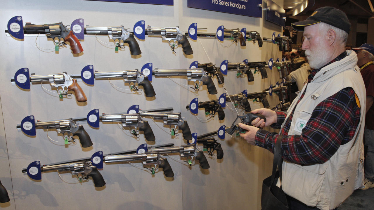 Homer Van Meter, of Rhineland, WI, inspects a revolver during the National Rifle Association's (NRA) 141st Annual Meetings & Exhibits in St. Louis, Missouri, April 13, 2012.   REUTERS/Tom Gannam (UNITED STATES - Tags: BUSINESS SOCIETY)