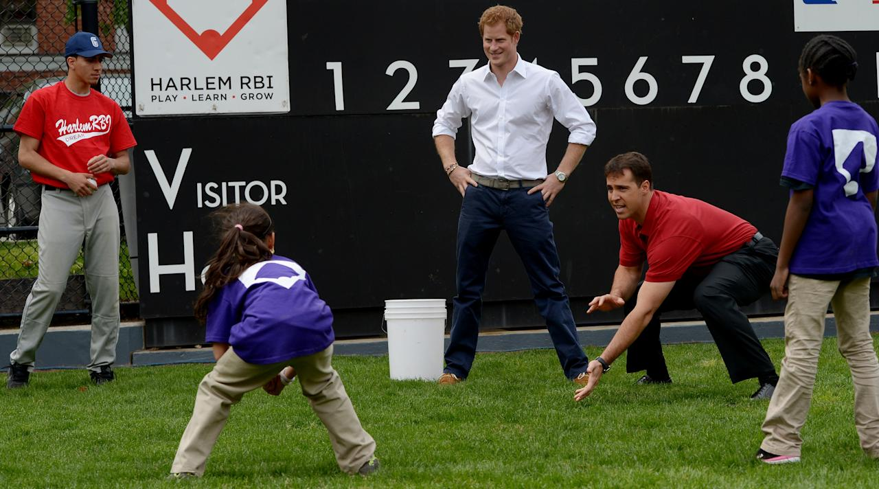 NEW YORK, NY - MAY 14:  HRH Prince Harry (3rd R) and New York Yankees baseball player Mark Texeria (2nd R) talk with young players while participating in a baseball clinic during the launch of a new partnership between the Royal Foundation of the Duke and Duchess of Cambridge and Harlem RBI, a local community organization May 14, 2013 in the Harlem neighborhood of New York City. HRH will be undertaking engagements on behalf of charities with which the Prince is closely associated on behalf also of HM Government, with a central theme of supporting injured service personnel from the UK and US forces.  (Photo by Justin Lane - Pool/Getty Images)