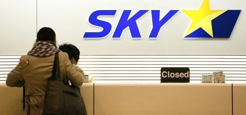 Woman checks in at a Skymark Airlines desk at Haneda airport in Tokyo