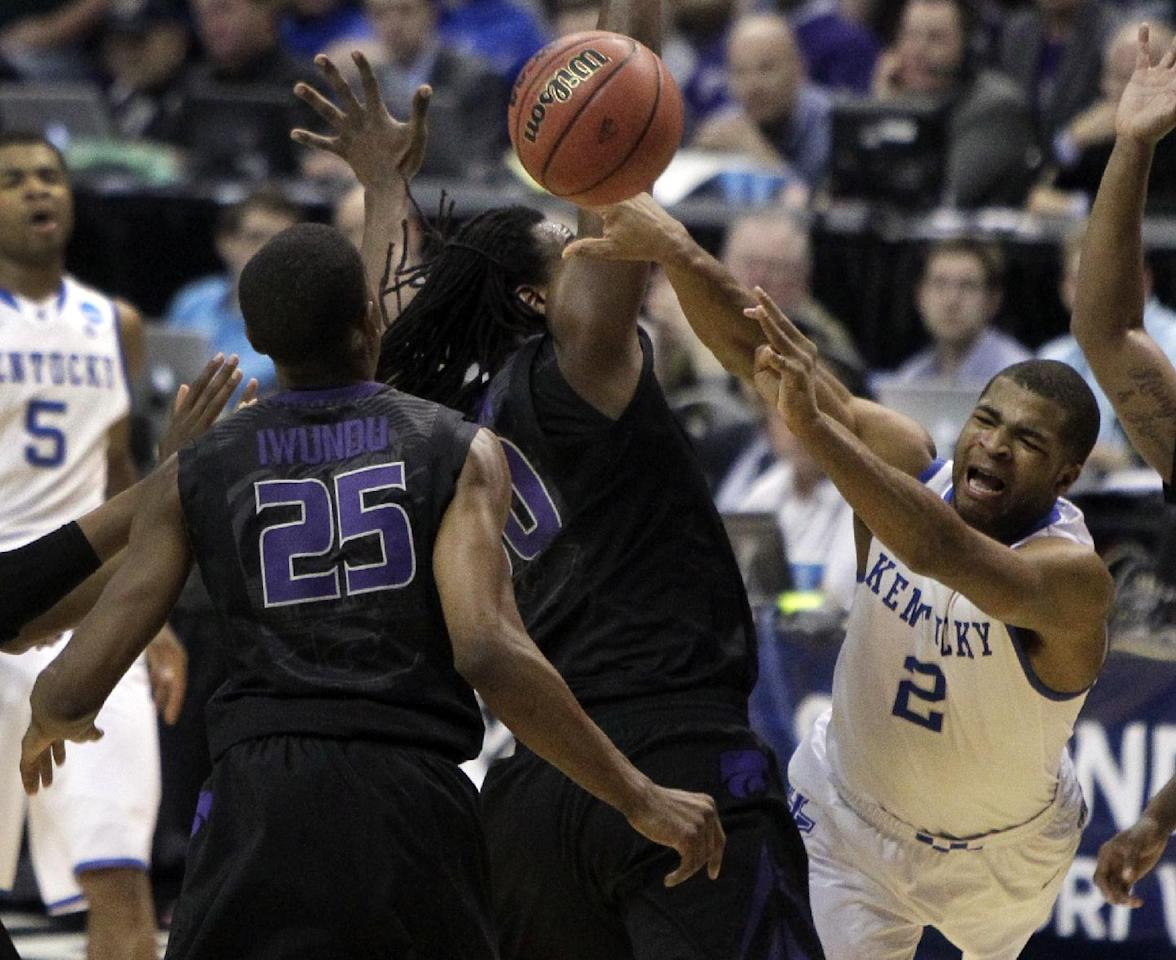 Kentucky's Aaron Harrison (2) loses control of the ball on his way to the basket as Kansas State's D.J. Johnson and Wesley Iwundu (25) defend during the first half of a second-round game in the NCAA college basketball tournament Friday, March 21, 2014, in St. Louis. (AP Photo/Jeff Roberson)
