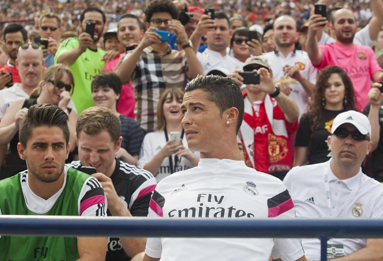 Real Madrid forward Cristiano Ronaldo, front center, sits with teammates on the bench before the first half of a Guinness International Champions Cup soccer match with Manchester United at Michigan Stadium, Saturday, Aug. 2, 2014, in Ann Arbor, Mich. (AP Photo/Tony Ding)