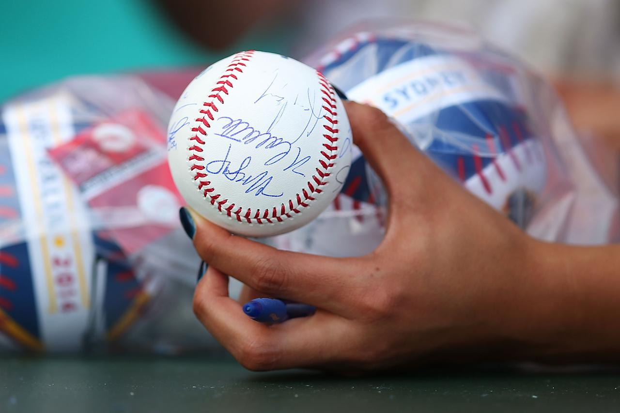 SYDNEY, AUSTRALIA - MARCH 23:  A fan holds a signed baseball during the MLB match between the Los Angeles Dodgers and the Arizona Diamondbacks at Sydney Cricket Ground on March 23, 2014 in Sydney, Australia.  (Photo by Brendon Thorne/MLB Photos via Getty Images)