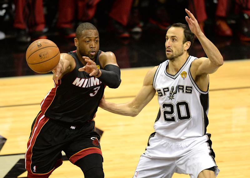 Dwyane Wade (L) of the Miami Heat passes the ball wile Manu Ginobili of the San Antonio Spurs guards him during Game 5 of the NBA Finals on June15, 2014 in San Antonio,Texas