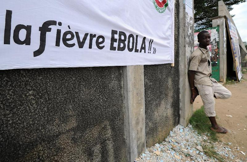 A man stands near a banner reading ''Ebola fever!!'' '' prior to a football tournament gathering youth from Guinea near the Koumassi sports center in Abidjan on August 10, 2014