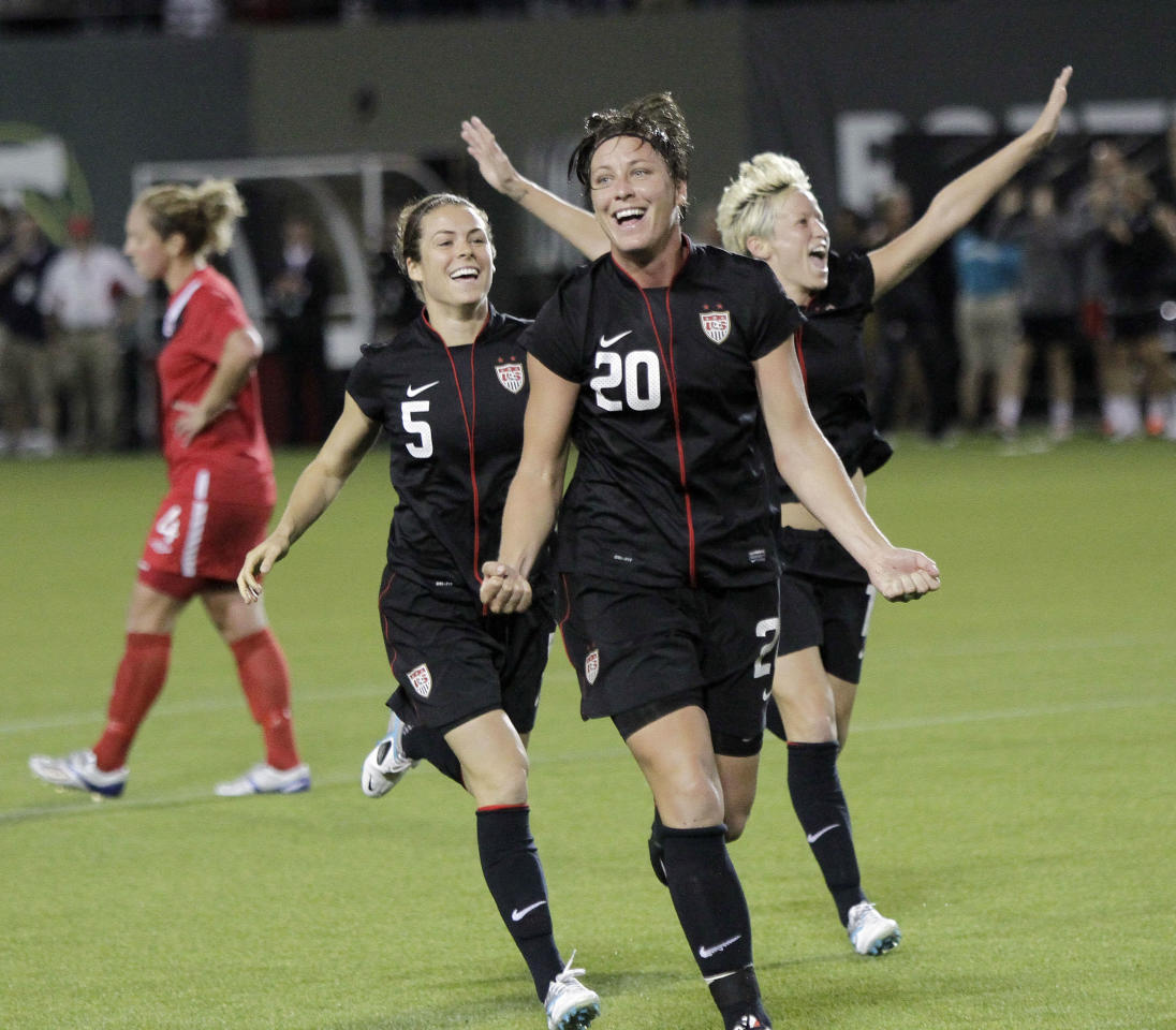 US Women's National Team forward Abby Wambach, middle, celebrates her goal with teammates Kelley O'Hara, left, and Megan Rapinoe during the second half of their Celebration Series soccer game against Canada in Portland, Ore., Thursday, Sept. 22, 2011. Wambach scored two goals as they won 3-0.(AP Photo/Don Ryan)