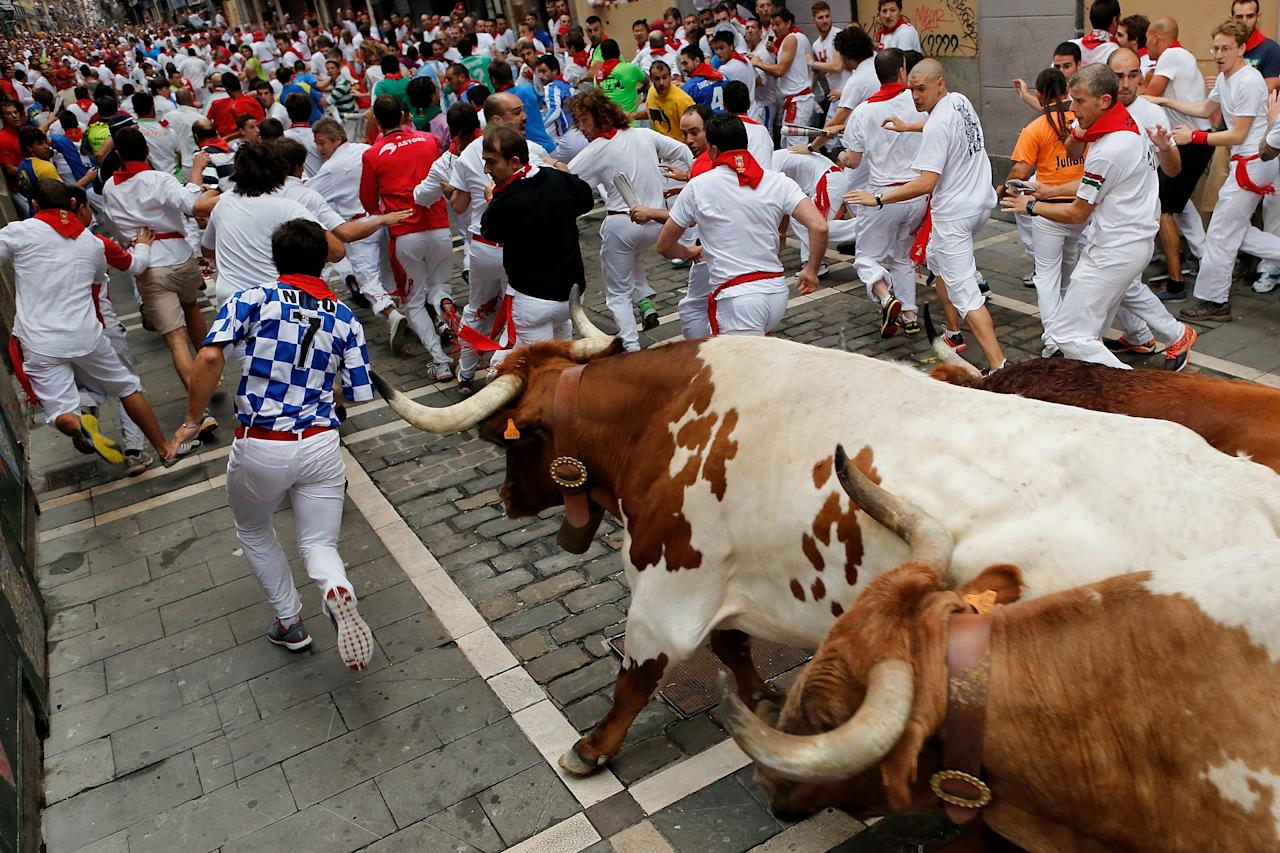 PAMPLONA, SPAIN - JULY 12: Revellers run with El Pilar's ranch fighting bulls at Curva Estafeta during the seventh day of the San Fermin Running Of The Bulls festival on July 12, 2013 in Pamplona, Spain. The annual Fiesta de San Fermin, made famous by the 1926 novel of US writer Ernest Hemmingway 'The Sun Also Rises', involves the running of the bulls through the historic heart of Pamplona, this year for nine days from July 6-14. (Photo by Pablo Blazquez Dominguez/Getty Images)
