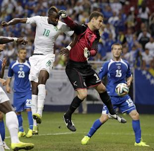 Bosnia goalkeeper Asmir Begovic, center, deflects a head ball away from Ivory Coast's Lacina Traore (18) as Bosnia's Toni Sunjic (15) watches during the first half in an international friendly soccer match Friday, May 30, 2014, in St. Louis. (AP Photo/Jeff Roberson)
