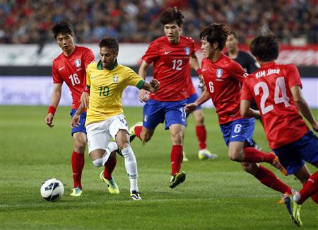 Brazil's Neymar fights for the ball with South Korea's players during their friendly soccer match at the Seoul World Cup stadium