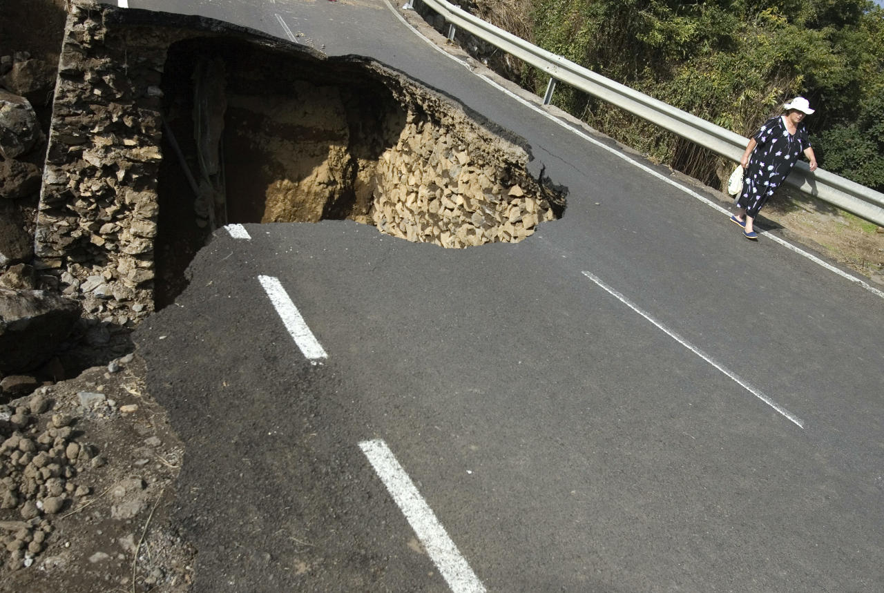A woman walks on the damaged TF326 road after a portion of it collapsed after storms, near the Palo Blanco village on Spain's Canary island of Tenerife November 23, 2009. Torrential rain hit several villages on November 16 in the north of Tenerife island, blocking some of the roads, damaging others as well as flooding homes and businesses.   REUTERS/Santiago Ferrero (SPAIN ENVIRONMENT IMAGES OF THE DAY) - RTXR1XU