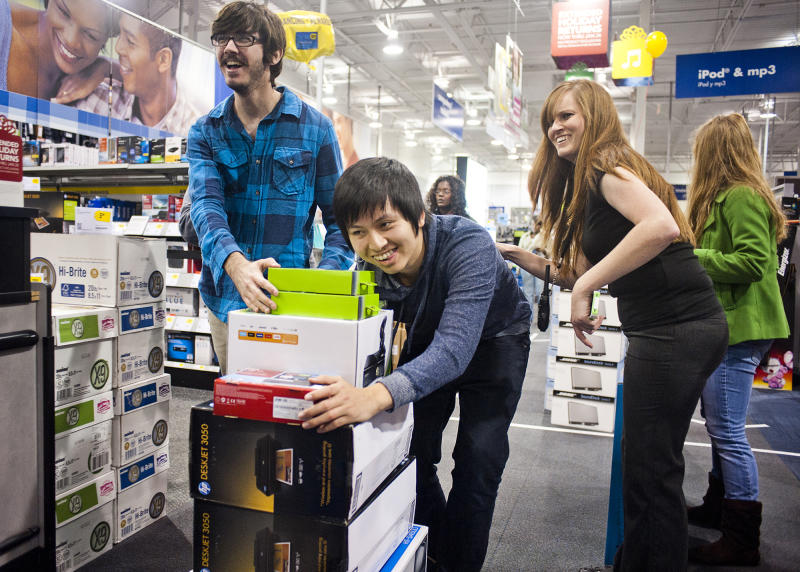 Shelby Buquet and Phi Nguyen, friends from Houma, push their items towards the cash register at the Best Buy electronics store during Holiday Black Friday shopping on Friday, Nov. 25, 2011 at midnight in Houma, La.  Black Friday sales began in earnest as stores opened their doors at midnight. (AP Photo, Michael Conti/The Houma Courier) NO SALES MAGS OUT