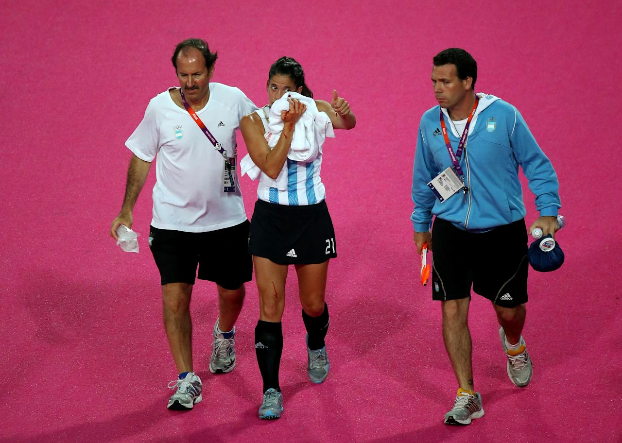 LONDON, ENGLAND - AUGUST 10:  Mariela Scarone of Argentina is escorted off the field after being struck in the face during the first half against the Netherlands during the Women's Hockey gold medal match on Day 14 of the London 2012 Olympic Games at Hockey Centre on August 10, 2012 in London, England.  (Photo by Daniel Berehulak/Getty Images)