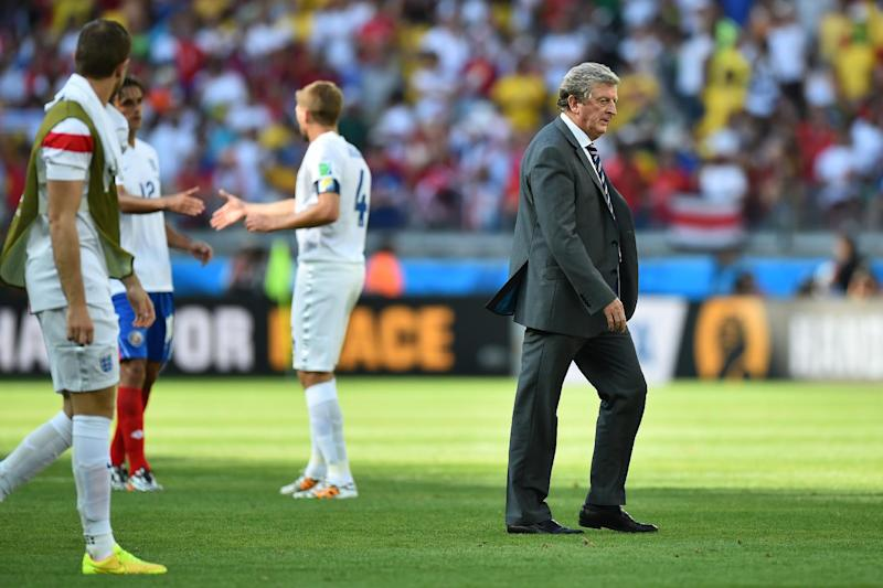 England's coach Roy Hodgson (R) walks on the pitch after the Group D football match between Costa Rica and England at The Mineirao Stadium in Belo Horizonte on June 24, 2014,during the 2014 FIFA World Cup