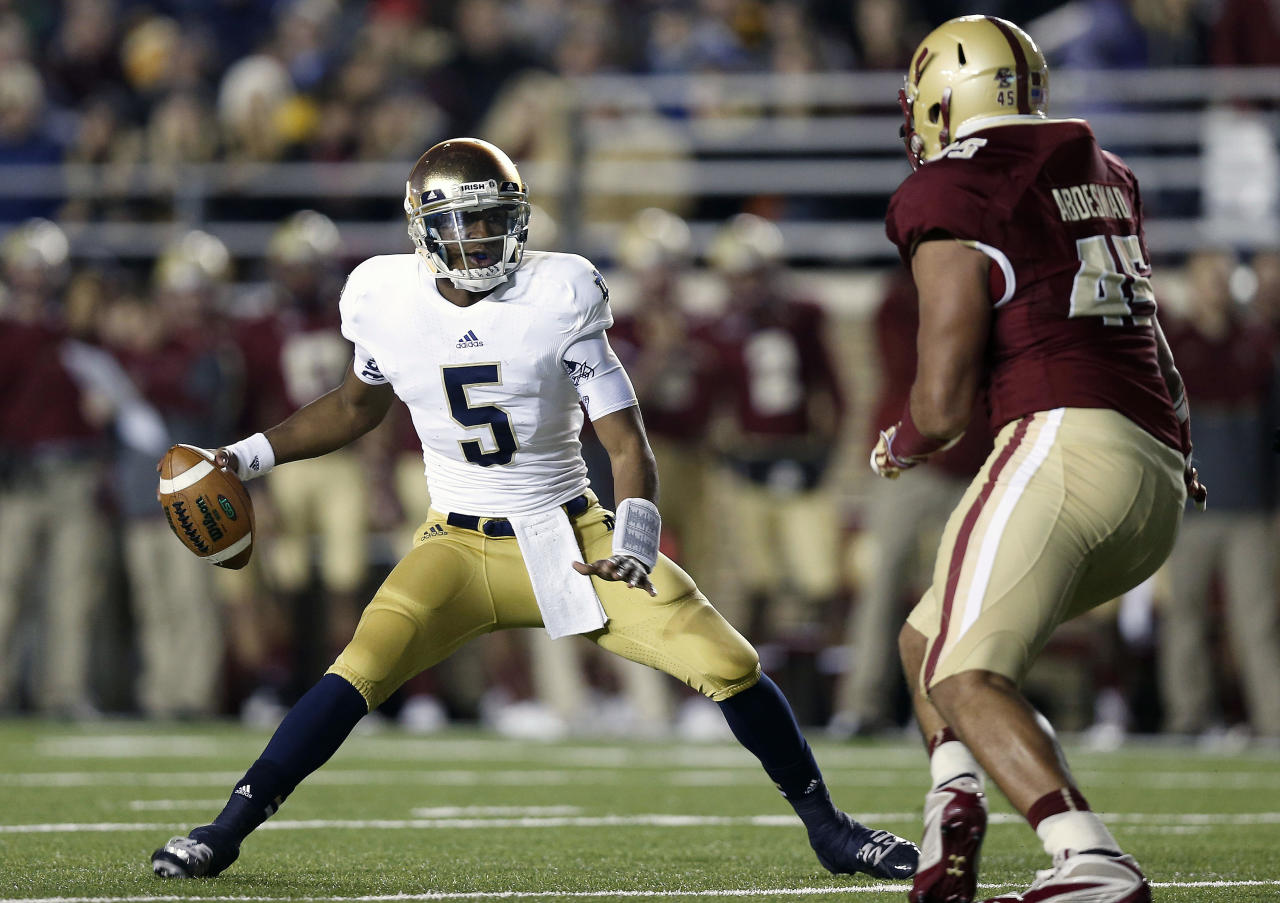 Notre Dame quarterback Everett Golson looks for an opening around Boston College Eagles defensive end Mehdi Abdesmad during the first half of an NCAA college football game in Boston on Saturday, Nov. 10, 2012. (AP Photo/Winslow Townson)