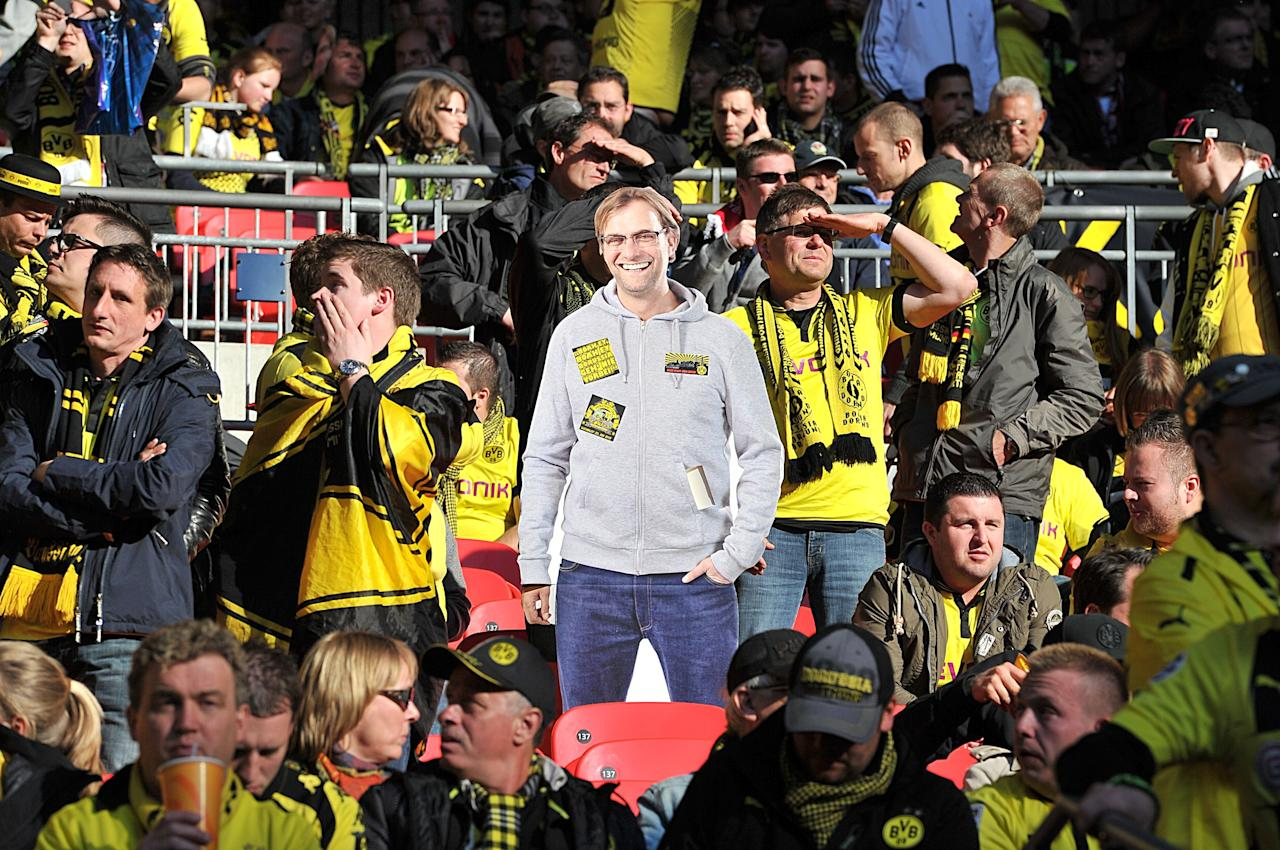 Borussia Dortmund fans in the stands with a cardboard cut out of manager Jurgen Klopp